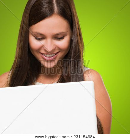 Portrait Of A Young Woman Holding A Computer against a green background