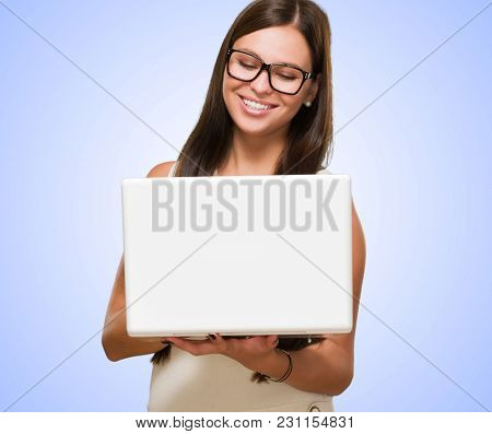 Portrait Of A Young Woman Holding A Computer And Wearing Specs against a purple background
