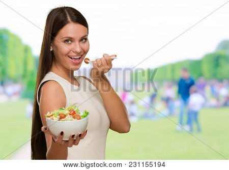 Portrait Of A Young Woman Eating A Salad at a park