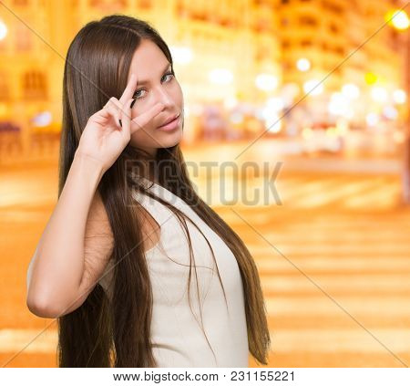 Beautiful Smiling Woman Showing Two Fingers In Front Of Eye at a city by night