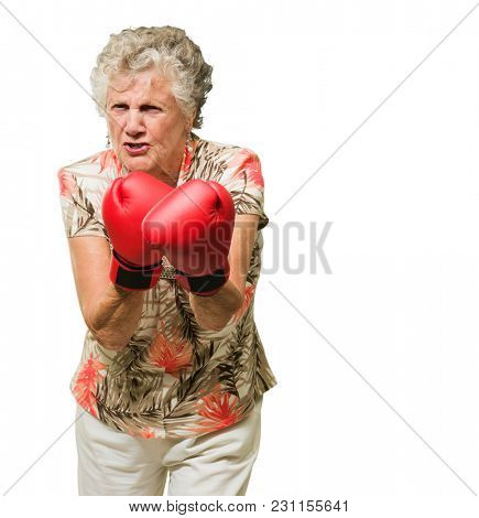 Angry Mature Woman Wearing Boxing Gloves On White Background