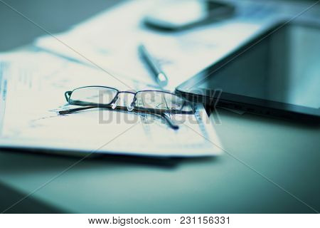 Business Financial Analysis Of The Workplace With The Glasses On The Documents In Office