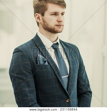 Newcomer Businessman In A Business Suit Stands Near The Window, Hands Folded In Front Of Him .the Ph