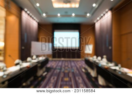 Blurred, Defocused Background Of Modern Conference Room With White Projection Screen. Company Meetin