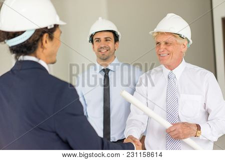 Man In Formalwear And Hard Hat Escorted With Young Colleague, Holding Blueprint And Shaking Hands Wi