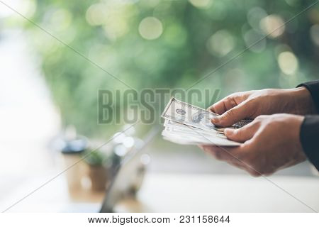 Portrait Of Confident Young Asian Businessman Looking To The Right Side. Hands Counting Dollar Bankn