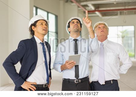 Young Serious Man In Helmet And Tie With Tablet Escorted With Two Engineers And Pointing At Building