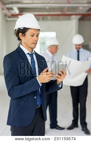 Man In Formalwear And Helmet Using Tablet, His Two Partners Reviewing Blueprint In Background. Owner