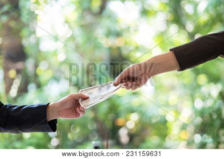 Corrupted Two Businessman Sealing The Deal With A Handshake And Receiving A Bribe Money. Hands Passi