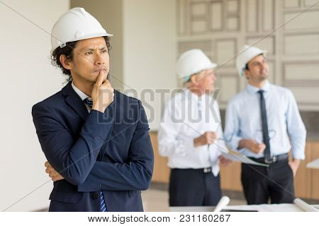 Portrait Of Pensive And Frowning Man In Helmet And Suit Touching Chin, While Two Engineers Discussin