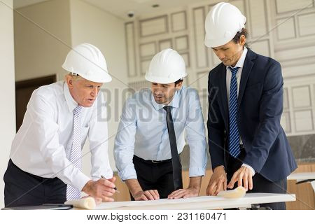 Three Men In Helmets And Formalwear Reviewing And Discussing Blueprint. Two Architects Consulting Pr