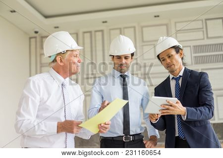Three Men In Helmets And Ties Meeting In Office With Papers And Tablet. Group Of Architects Attentiv