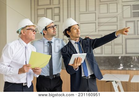 Three Men In Ties And Hardhats Surprised With Window Scene. Property Investor Visiting Site And Impr