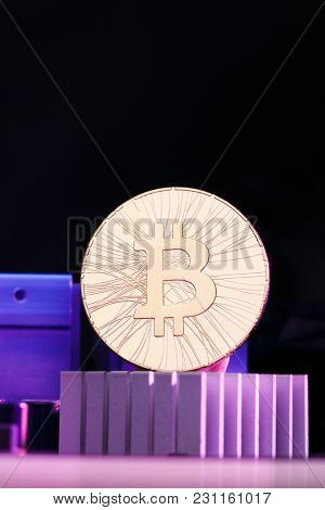 Photo of golden bitcoin and processor on pink background