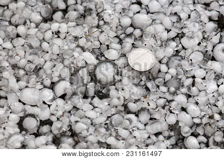 hail sized with a larger coin, hailstones on the ground after hailstorm, hail of great size
