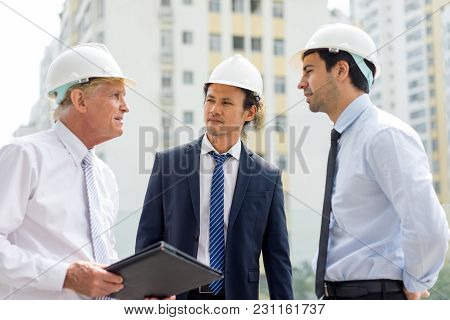 Two Men In Ties And Helmets Explaining Something To Serious Man In Suit. Supervisor Inspecting Const