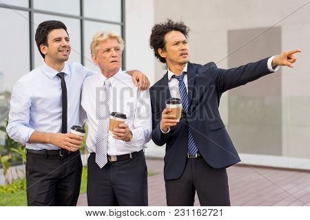 Closeup Of Business Team Of Three Diverse People Looking At Something, Holding Drinks In Disposable
