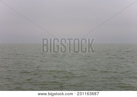 Bad Weather Over A Lake With A Gray And Characterless Sky. Minimalist Image With Half Of Water And H