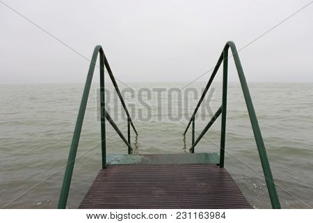 Bad Weather Over A Lake With A Gray And Characterless Sky And With A Pier Stairs To The Lake.