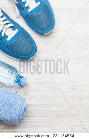 Fitness concept background with sneakers water bottle and towel. Top view with space for your text