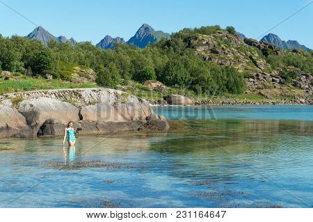A Girl In A Swimsuit With A Camera In The Turquoise Transparent Water Of The Bay Against The Backgro