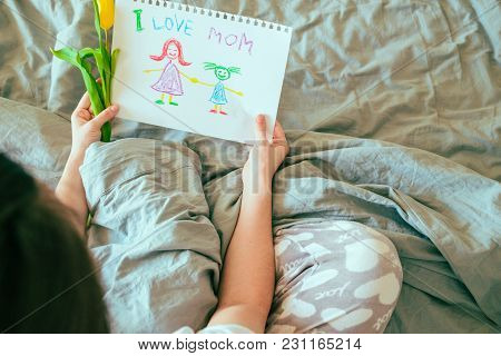Woman Sit In Bed And Look At Picture That Kids Drew For Mother Day