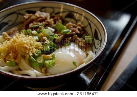 Close-up Of A Bowl Of Beef Udon With Soft-boiled Egg, Chives And Tempura Crumbles.
