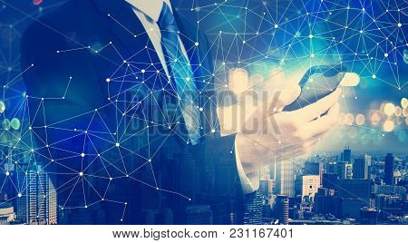 Double Exposure Of Business Man With Smartphone And City Background