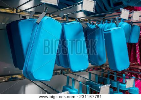 Many Rows Of Blue Pencil Boxes Hanging On Metal Rack In Wholesale Store.