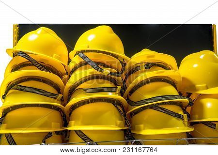Stacks Of Yellow Safety Helmets With Elastic Strap In A Row On Shelf.