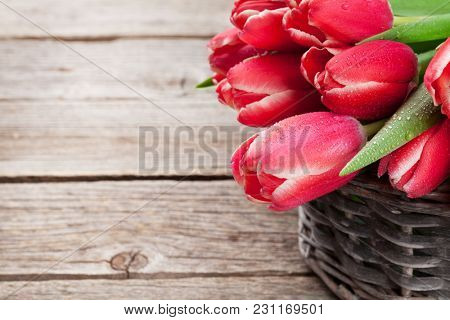 Red tulip flowers bouquet on wooden background. Easter or Valentine's day greeting card. With space for your greetings