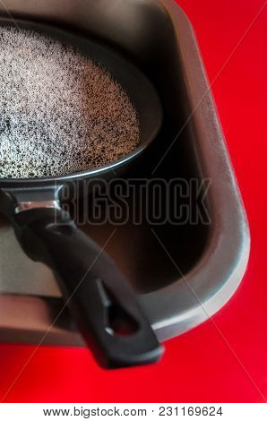 Household Chores Shown As Unwashed Skillet With Lather And Bubbles On A Red Kitchen Countertop.