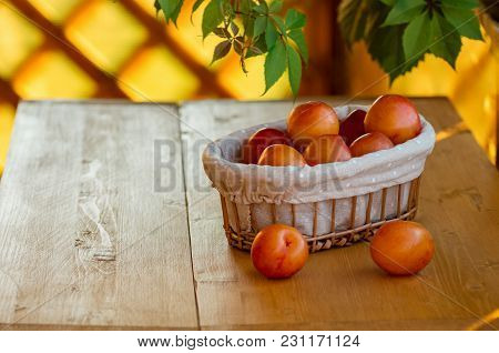 Ripe Yellow Plums In A Wicker Basket On A Wooden Table