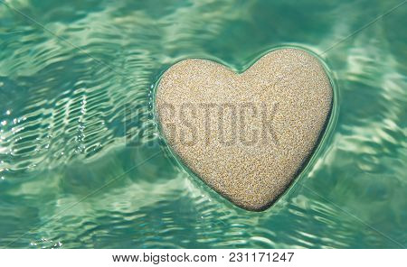 Heart Made Of Sand Floating In Transparent Turquoise Ocean Ripples Water Background, Saint Valentine