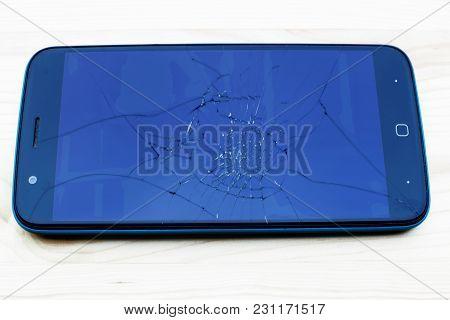 Smartphone With Broken Screen On Wooden Background.