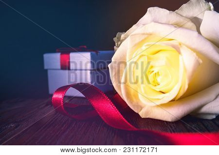 Gift Box With Reed Bow And White Or Yellow Rose Flower On Vintage Wooden Table With Dark Background.