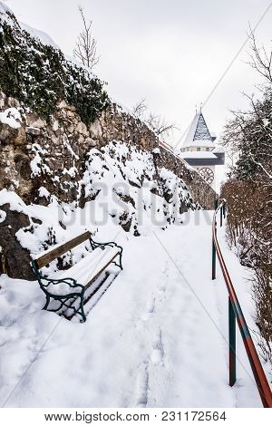 Snow Covered Bench And Path To Uhrturm Clocktower Landmark Of City Graz On Hill Schlossberg In Winte