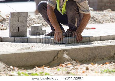 Worker Puts Sidewalk Tile On The Road .