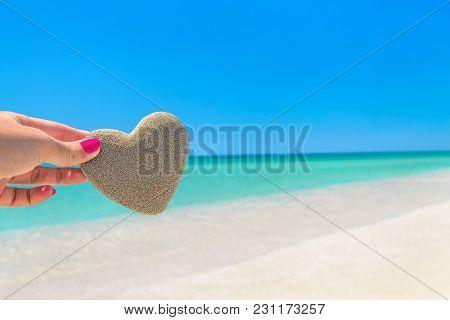 Heart Made Of Sand In Womans Hand Against Tropical Ocean Beach Background. Romantic, Love, Honeymoon