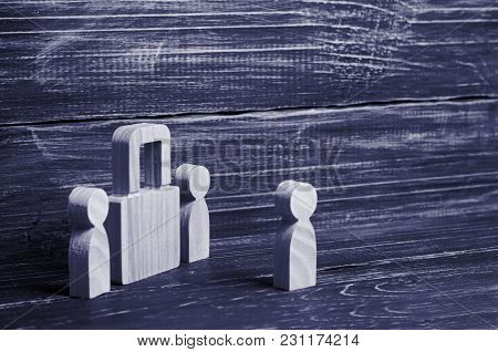 Two People Stand Near A Padlock And Keep Secrets, Information, Entrance. Wooden Figures Of Persons C