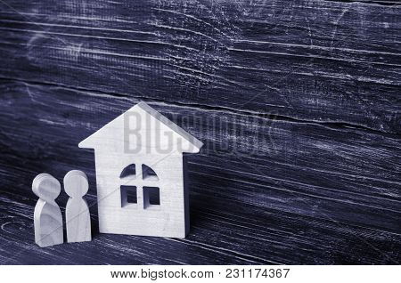 Two People Are Standing Near The House. Wooden Figures Of Persons Stand Near A Wooden House. The Con