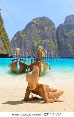 Young woman sitting on the beach at Maya Bay on Phi Phi Leh Island
