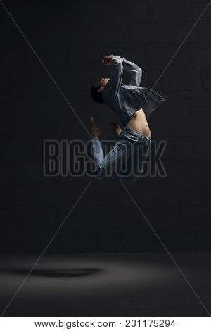 Girl With Shot Haircut In Jeanswear Dancing Gracefully In Dark Room Full-length Shot