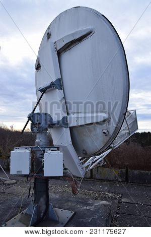 Outdated Satellite Dish From The Back View On The Roof