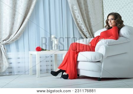 Beautiful Young Pregnant Woman In Red Dress Posing