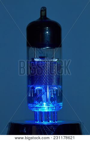 Colorful Led Light Illuminates An Electron Tube Against A Dark Background From Below.