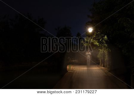 Double Exposure Night Scene Of Person Walking Dark Street Illuminated With Streetlights. The Recedin