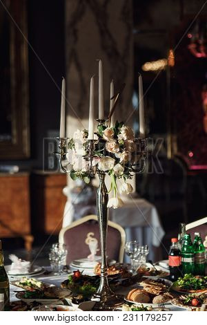 Pink Rose Petals Ligh Between White Candles Standing On The Dinner Table