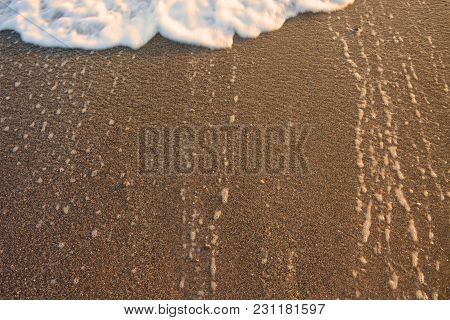 Wave Moving On The Sand. Sea Water Drops And Foam Background On The Sunset. Tide Of Wave