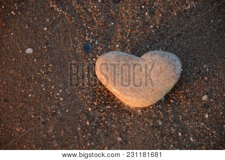 Stone Heart On The Pebble Beach. Love Concept. Valentines Background Closeup